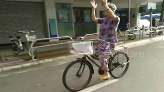 Elderly woman claps her hands in the air while riding a bike - Video