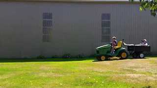 Young Son Takes Injured Dad for a Ride While Mowing the Lawn - Video