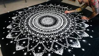 Artist recreates huge mandala symbol using only salt