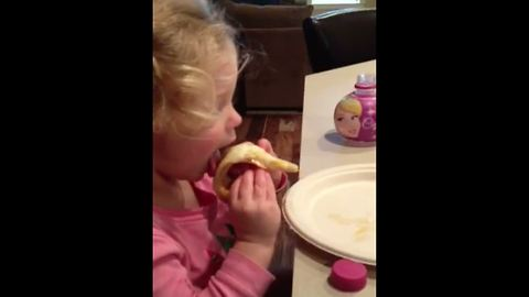A Tot Girl Struggles To Put A Slice Of Pizza In Her Mouth