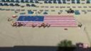 Terry cloth American flag tribute lines beach in front of TradeWinds Island Resort - Video