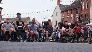 Boozy competitors race around UK town in wheelbarrows drinking beer along the way