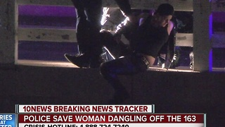 Police save woman dangling off Highway 163 - Video