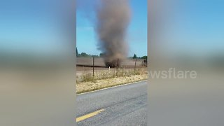 Huge dust devil swirls across field - Video