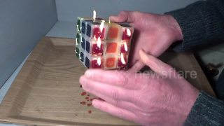 Man plays with burning candle Rubik's Cube - Video