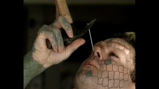 Lizardman Hammers Nail Up Nose - Video