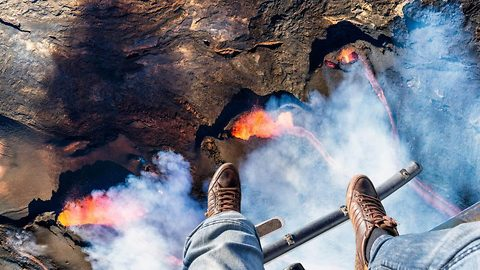 It's getting hot up here: Adventurous photographer dangles dangerously above erupting volcano for up-close glimpse of fearsome inferno