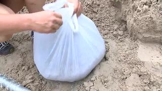Residents improvise when sandbags run out to protect their homes | Digital Short - Video