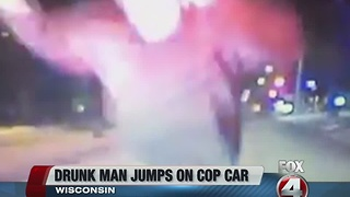 Man drunkenly charges at police car - Video
