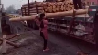 Tiny woman carries gigantic tree trunk!