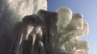Leaking pipe creates 10m-high frozen waterfall at abandoned building - Video