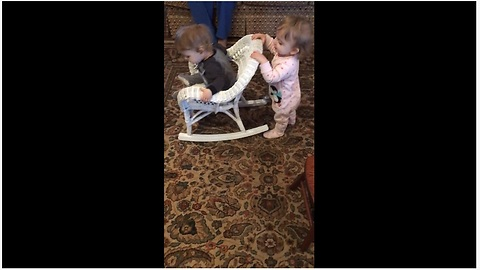 Baby girl pushes twin brother in rocking chair