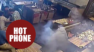 Moment a man's shirt goes on fire in a restaurant - after his mobile phone explodes in his pocket - Video