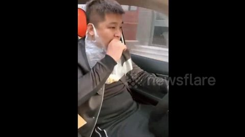 Driver heaves food waste into plastic bag wrapped around his ear