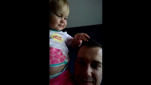 Baby extremely intrigued by daddy's new haircut