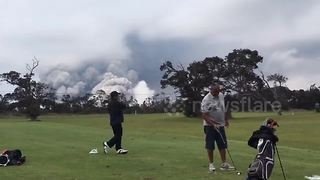 Golfers undistracted by volcano's massive ash plume behind them - Video