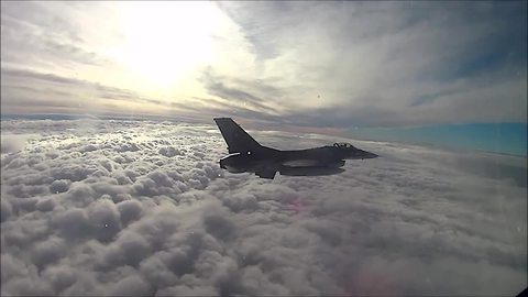 Cockpit view of F16 Fighting Falcon above a sea of clouds