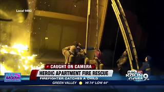 Firefighter catches child escaping from apartment fire - Video