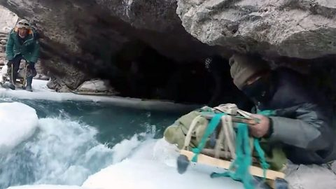 Breathtaking moment adventure junkies precariously cross frozen river at altitude of 11,000 feet