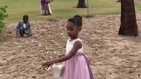 A Tot Boy Cleans Up After A Flower Girl At A Wedding