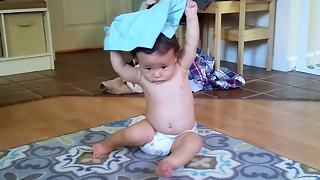 Persistent baby repeatedly puts pants on his head - Video