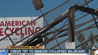 Crews try to remove billboard that nearly crashed on people - Video