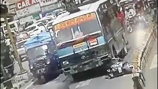Scooter rider walks away after falling under bus - Video