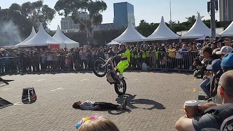 Biker performs tricks over a girl