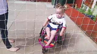 Three-year-old girl plays football in her wheelchair