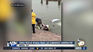 Crews rescue woman from submerged car - Video