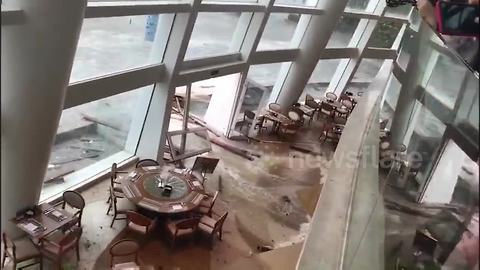 Hotel guests look on in horror as floodwaters crash into dining room