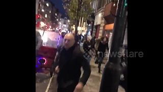 Ground shot of people running from London's Oxford Circus
