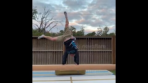 Daughter supports her dad as he attempts to cartwheel on a balance beam in Australia
