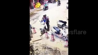 Man drives motorcycle carrying two children and mother into sinkhole - Video