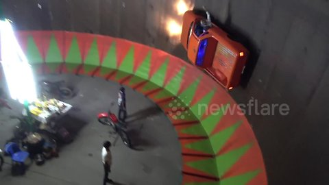 Pick-up truck takes on motorcycle wall of death at Thai fair