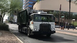 Waste Management roll off truck driving bye.