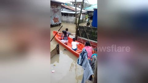 Children use boat to get around village during flooding in the Philippines
