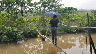 """Young woman tries to cross """"monkey bridge"""" over a river"""