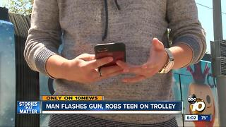 Man flashes gun, robs teen on trolley - Video