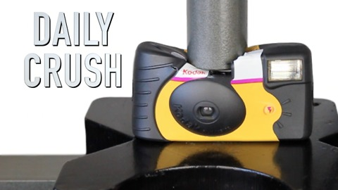 Crushing a disposable camera with hydraulic press