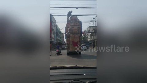 Passenger scales car with furniture stacked 20ft high to clear power lines