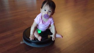 A Baby Girl Having Fun Riding A Roomba Vacuum
