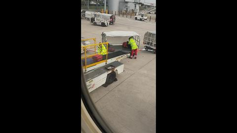 Baggage handlers at Manchester Airport toss suitcases over cart