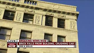 Concrete falls off downtown building, hits car - Video