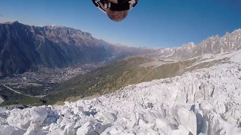 Heart-pounding POV footage shows base jumper shooting through sky above glaciers