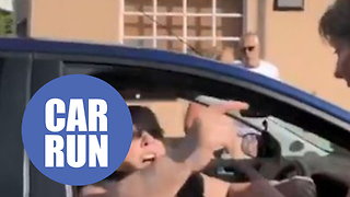 Frustrated woman drives into a half marathon and is stopped by runners - Video
