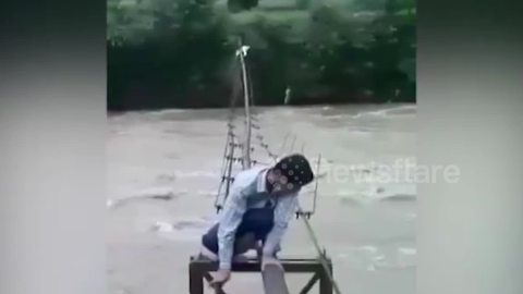 Students in India cross flooded river crawling on top of shaky pipeline