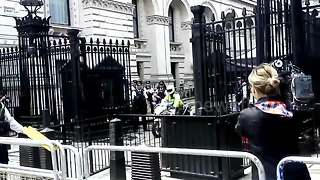 People protest outside Downing street as Theresa May leaves to meet the Queen - Video