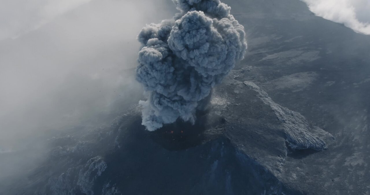 Drone captures incredible footage of man running towards erupting volcano