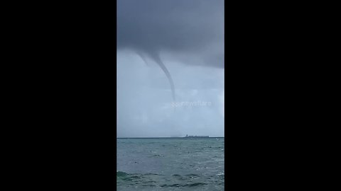 Water spout looms low over cargo ship